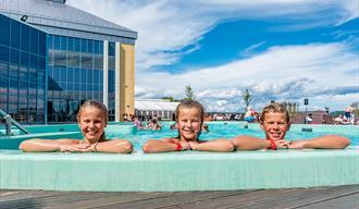 3 barn ser over bassengkanten på utendørsbasseng til Badeparken på Quality Hotel Skjærgården i Langesund