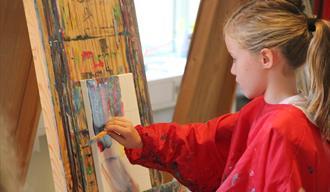 Barneverksted Telemarksgalleriet. En liten jente som maler på lerret
