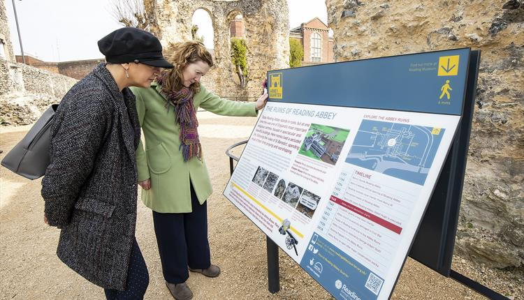 Two people reading information boards in Reading Abbey
