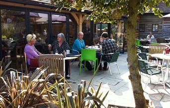 Customers sitting on garden patio at Steff's Kitchen at Fairweather's Garden Centre in the New Forest