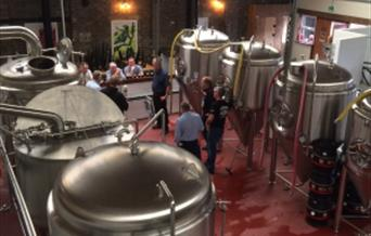 A tour taking place in the brewery. You can see the Tap Room just behind the brewery. The very highly rated tours (averaging 5/5 on Trip Adviser) Tour