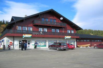 Jokerbutikk i nederste etasje i en rødmdalt sveitservilla.