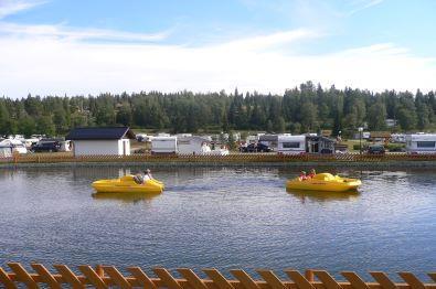 Bjørkestølen camping med vanndam i forkant med barn som trår på pedalbåt en fin sommerdag.