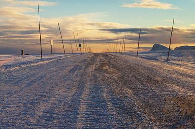Snow-covered road in the sunset wit a mountain in the background