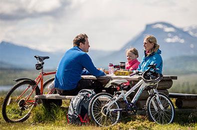 En familie med sykler raster ved en benk|
