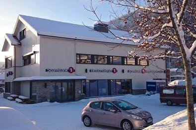 Et hvit trebygg som huser Sparebank1 Valdres Hallingdal i morgensola en vintermorgen.