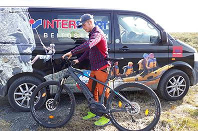 A person with an e-bike is standing in front of a van with the Intersport logo imprinted