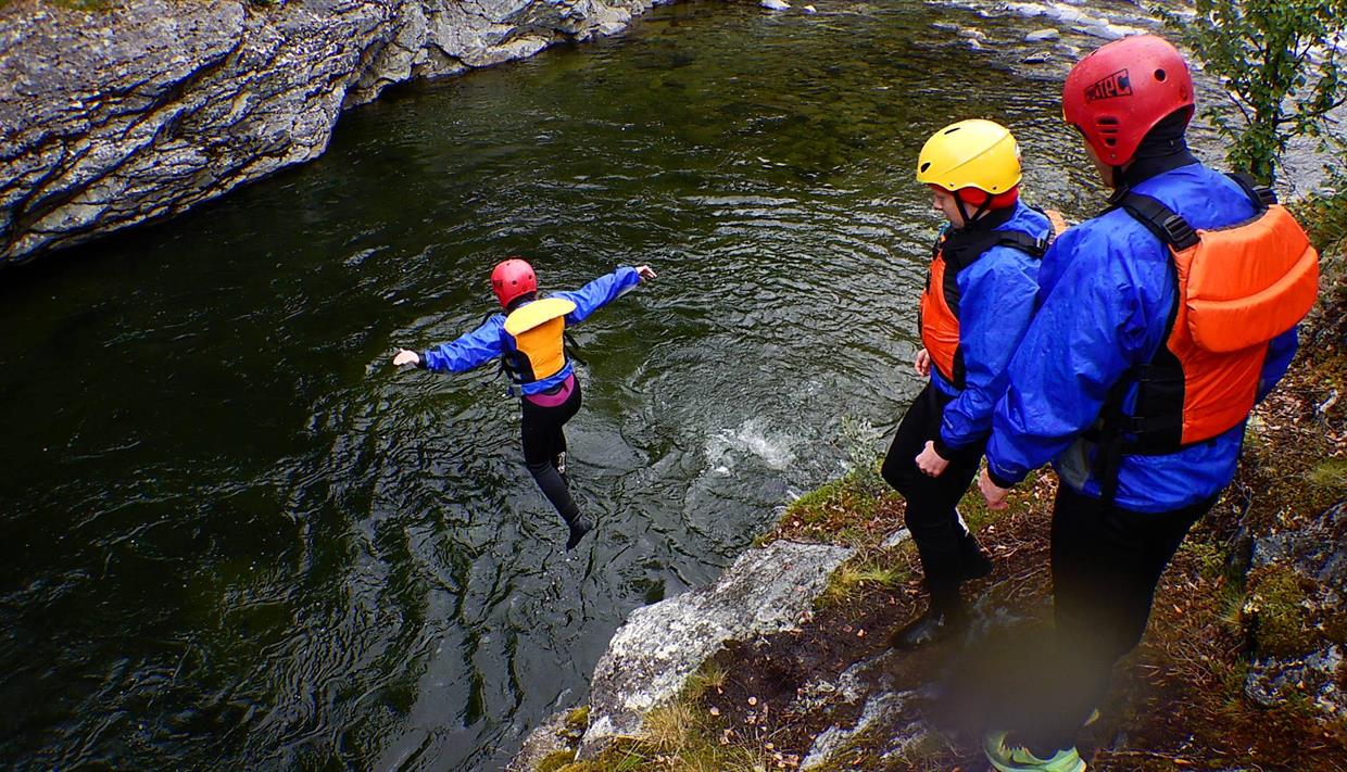 A person jumping from a cliff into a pool in the river while to others watch.