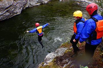 En person hopper fra en klippe ned i elva mens to andre ser på.