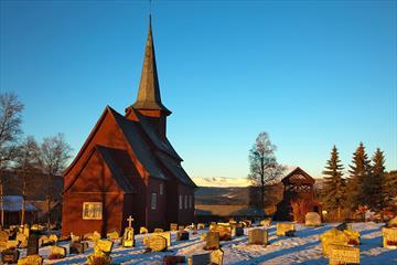 En stavkirke i en snødekt kirkegård i vintersolskinn.