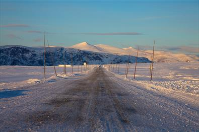 The road across Valdresflye in warm sunlight during early winter. In the background white sugartop mountains (Nautgardstinden and Stornubben) rise abo