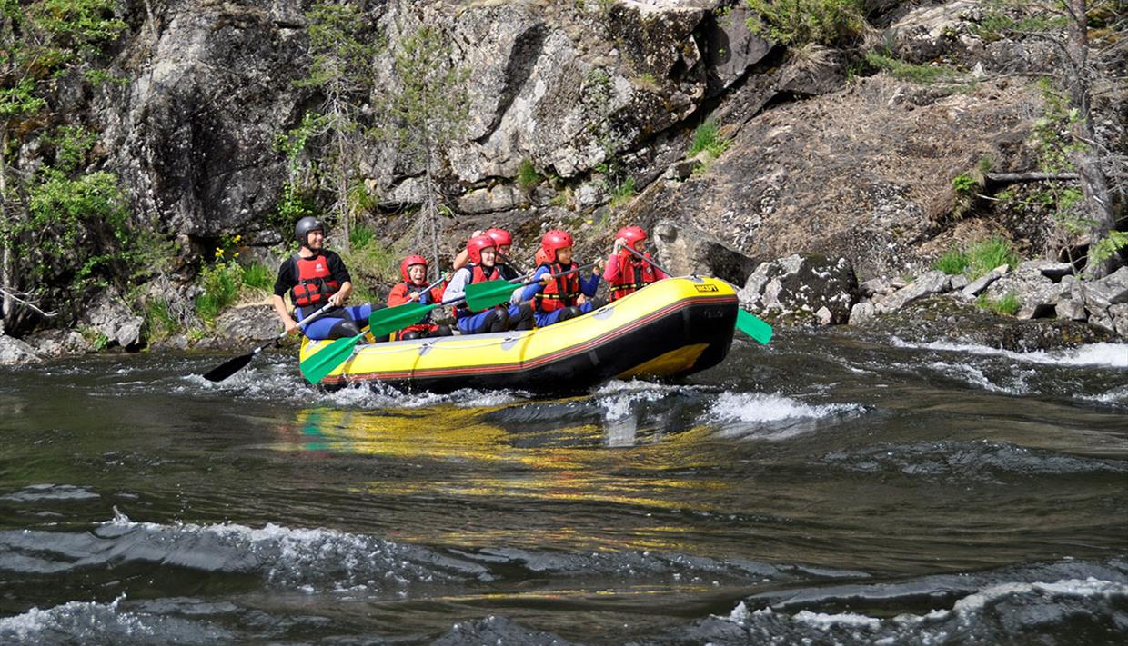 A yellow raft on a river passes a rock face