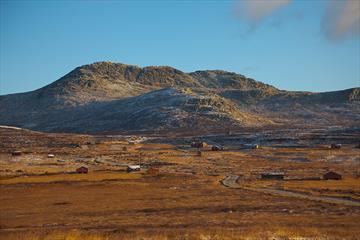 Skaget reiser seg over stølslandskapet ved Vesleskag. Det er høstfarger i fjellet og det første dryss av nysnø på toppen.