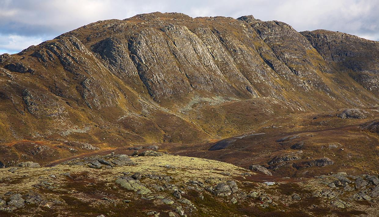 The summit point of Horntinden is located on a long mountain ridge, showing its steep flank to the photographer, while the trail leads up on the less