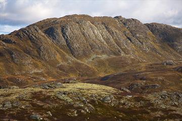 Horntind er høyeste punkt på en mektig fjellrygg som reiser seg over omgivelsene, brattsiden vendt mot fotografen. Stien går opp den slakere baksiden.