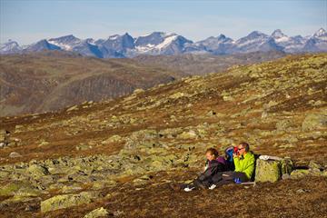 En familie tar en pause i gresset på et fjellplatå mellom mange lavdekte steiner på en solrik høstdag. Høye, spisse fjell i bakgrunnen.