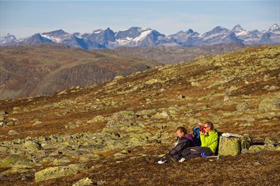 Eine Familie macht eine Pause im Gras zwischen flechtenbewachsenen Steinen auf einer Hochebene an einem sonnigen Herbsttag. Am Horizont hohe, spitze Berge.