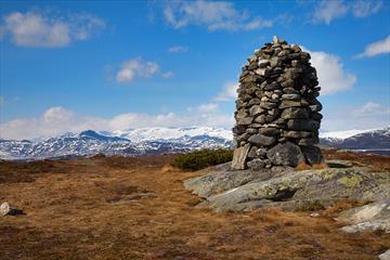 Den staselige, forseggjorte toppvarden på Javnberget ruver i fogrunnen, mens man ser Jotunheimen med snødekte fjell i horisonten.