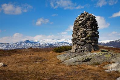 The enormous, nicely stocked summit cairn on Javnberget dominates the foreground, while Jotunheimen and its snow-covered 2000m-peaks cn be seen in the