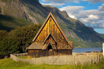 Øye stavkirke om sommeren. Innsjø og fjell i bakgrunnen.