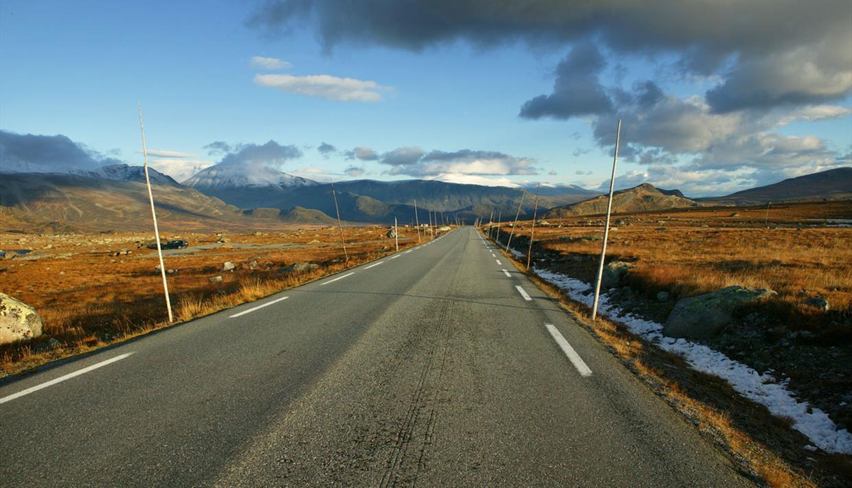 Die Straße über die Hochebene Valdresflye an einem sonnigen Herbsttag. Die Zweitausender im Hintergrund sind vom ersten Neuschnee bedeckt.