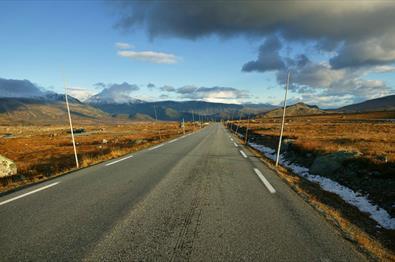 Veien over høysletten Valdresflye en solrik høstdag. Totusenmetertoppene i bakgrunnen er dekket av det første nysnødrysset.