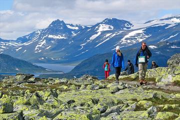 Vandrere i fjellet går gjennom et parti med masse lav på steinene. I bakgrunnen et vann og totusenmetertopper.