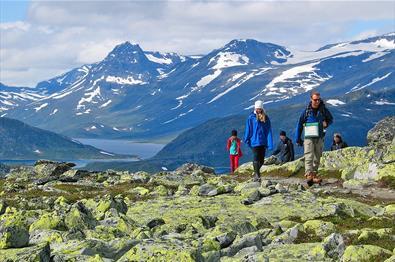 Wanderer im Gebirge passieren ein flechtenüberwachsenes Steinfeld. Im Hintergrund ein Bergsee und hohe Berge.