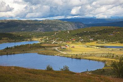 Idyllic surroundings with farm roads, cabins and lakes at Nordre Fjellstølen. In the background the Makalaus mountain massif with its steep hillsides