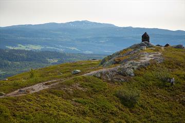 Siste stykke mot toppvarden på Jutulen med skogkledde lier og en fjelltopp i bakgrunnen.