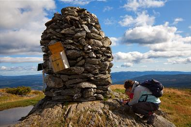 A large summit cairn on Synet. A mother and a child register their trip in the tour log book.