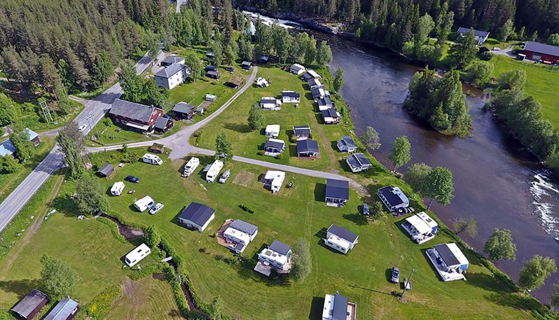 Dronebilde av campingplassen. Idyllisk beliggenhet langs elva.