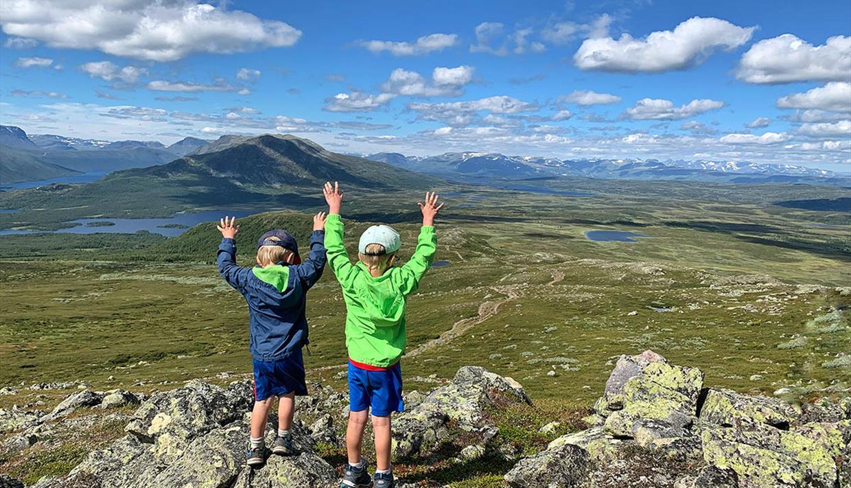Barn som nyter utsikten over fjell og vann fra toppen av Grønsennknippa.
