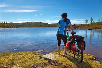 Kvinne syklist i blå sykkeltrøye står ved siden av sykkelen sin og ser utover et blått vann.