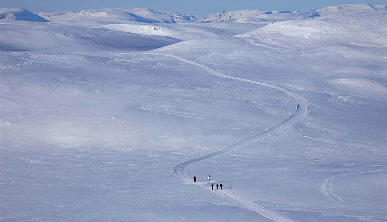 Skiløype som strekker seg over en fjellvidde med høye fjell i bakgrunnen.