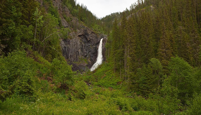 Der wasserfall Juvfossen fällt über eine Felsenklippe inmitten von üppiger grüner Vegetation.