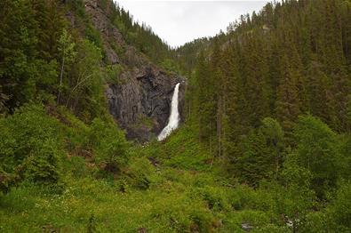 Juvfossen faller ned over en fjellskrent i frodig grønn vegetasjon.