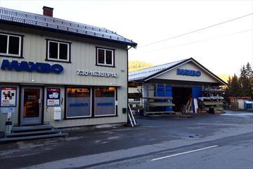Byggevareforretning med varelager fra utsiden. Bygget er kledd i lyst trepanel.