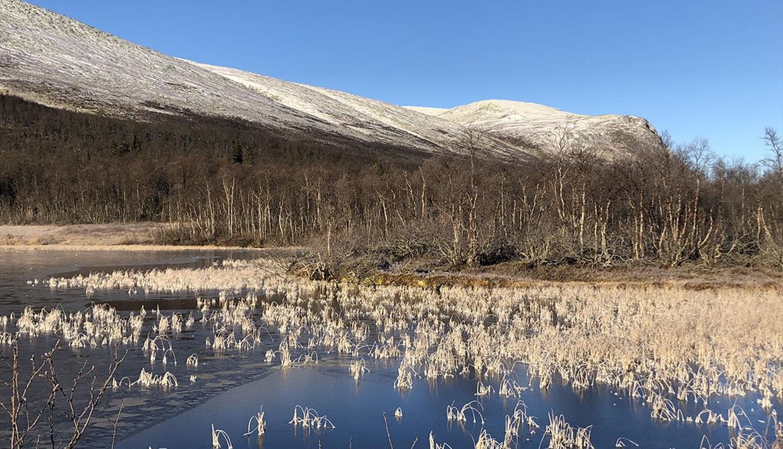 Tidlig høstmorgen ved Matkista. Isen har lagt seg på vannet, og snøen ligger på fjelltoppene.