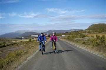 Two cyclists in colourful jackets cycling across the open mountainous landscape of the mountain farming area Stølsvidda along the Mjølkevegen cycling