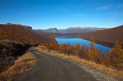 Im Anstieg der Straße über das Smådalsfjell mit Aussicht über den spiegelblanken Helin. Die Birken ind en Berghängen tragen orange Herbstfärbung. Blauer Himmel.
