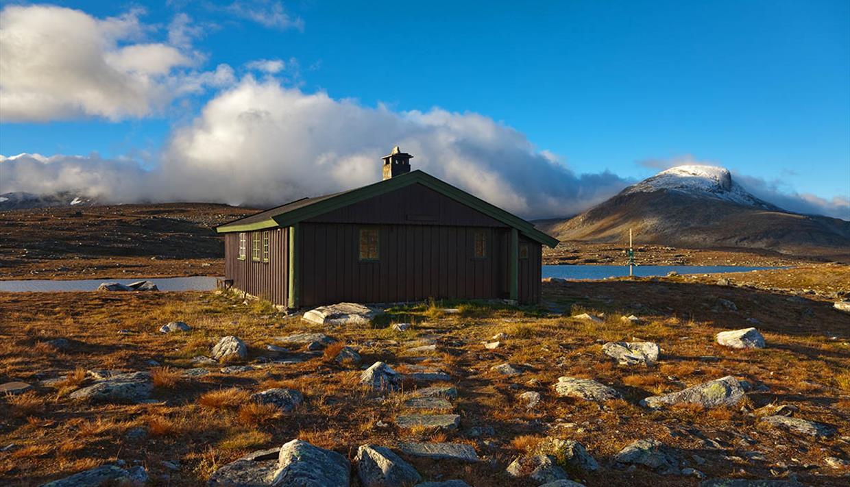 Sulebu en fin høstdag. Hytta ligger rett ved et lite vann, og fjelltoppene troner i bakgrunnen