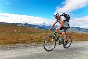 Radfahrer auf dem Slettefjellvegen mit Jotunheimens Bergen im Hintergrund.