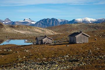 Tomashelleren en flott høstdag. To gråfargede hytter ved et lite vann, og ruvende fjelltopper i bakgrunnen.