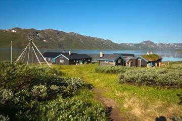 Husene på Torfinnsbu ligger idyllisk til ved Bygdin.