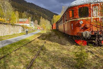 På gamle Bjørgo stasjon står fortsatt et gammelt togsett bestående av et lokomotiv og et par vogner på den gamle, gressbevokste skinnegangen. En syklist sykler på gangveien ved siden av.