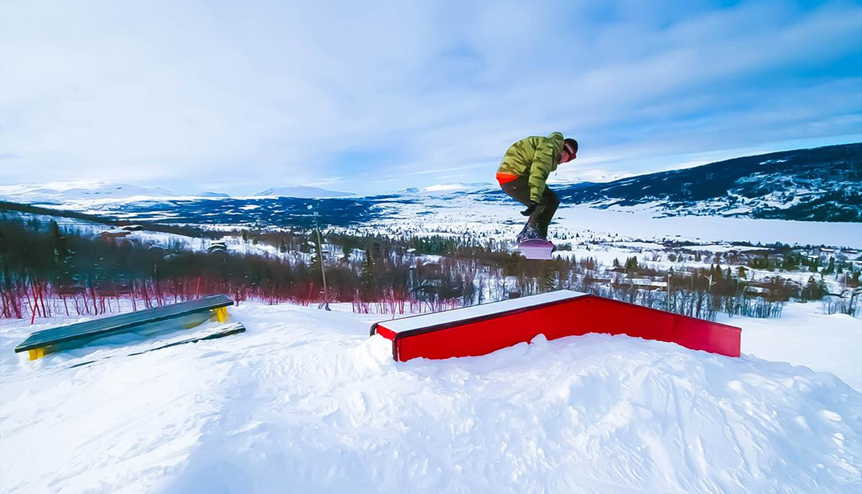 A snowboarder jumps over rails and elements in the ski center at Vaset.