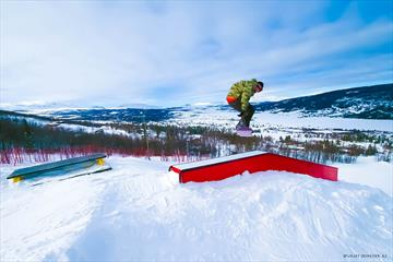 Ein Snowboarder macht Tricks mit Rails und Sprungelementen im Skicenter von Vaset.