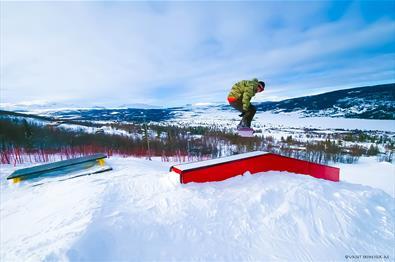 En snøbrettkjører gjør et triks på elementer i fun parken i skisenteret på Vaset.