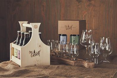 A wooden box with beer bottles and a number of beer glasses arranged on a hemp cloth.